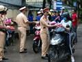 """Cảnh sát giao thông """"xuống đường"""" tặng nước, áo mưa cho sĩ tử TP.HCM"""