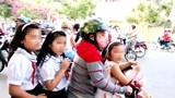 Cha mẹ chở con đầu trần đi qua trước mặt lực lượng tuần tra mà không bị xử phạt