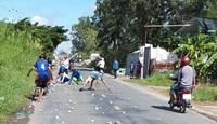 Người dân cùng tài xế xe tải nhặt đá rơi vãi trên quốc lộ