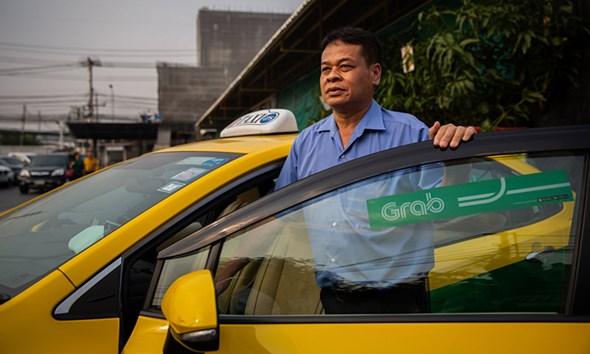 Thongsuk Thongrat đứng bên cạnh chiếc taxi của ông tại Bangkok hôm 25/2. Ảnh: NY Times.