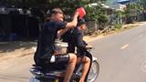Hai thanh niên vừa chạy xe máy vừa gội đầu bị xử phạt 1,5 triệu đồng