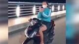 Cô gái vừa lái xe máy vừa thả tay ''múa quạt''